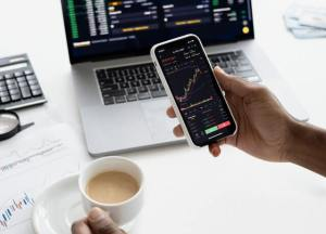 person holding phone and coffee with crypto charts, laptop with charts