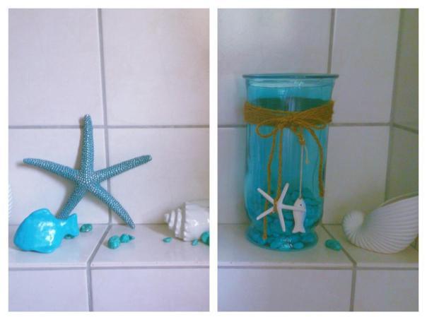 Selbstgebastelter Fisch aus Fimo in karibischem ozeanblau als Deko zwischen Muscheln und Seestern. Hellblaues Glas mit Steinen am Boden, dekoriert mit Fisch und Seestern.