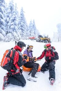 Ski patrol team rescue woman skier with broken arm