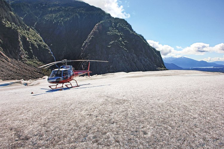 A helicopter lands on the glacier