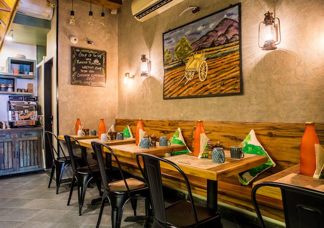 the farmers cafe is not your run of the mill healthy eatery designed snuggly the cafe has warm bamboo interiors carved woven and painted into murals to