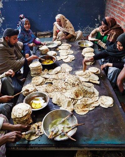 Volunteers make piles of parathas