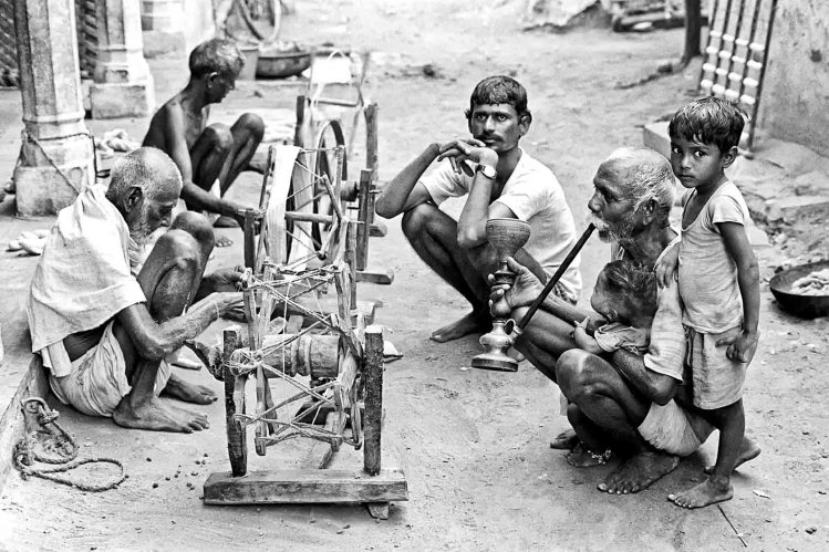 Weavers spin cotton into yarn at their spinning wheels in a village to make hand spun fabric, 1984