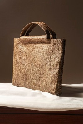 Hand-stitched bag made from Malai with cane handles. Marigold flower petals mixed with indigo extract create the rich shade