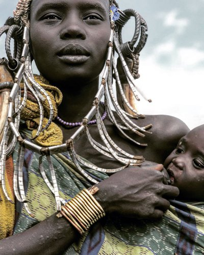 A Young Mursi Woman with a Child