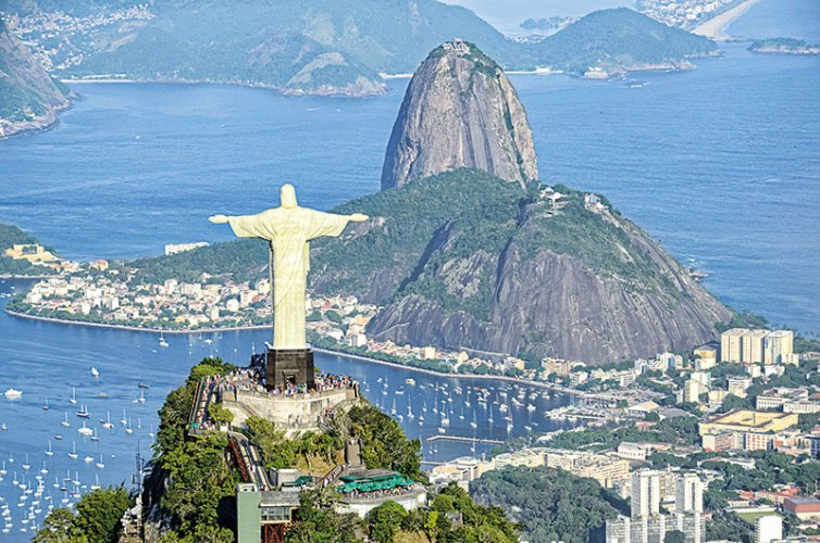 The iconic statue of christ the redeemer watches over the landscape of Rio de Janeiro