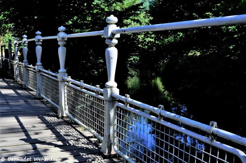 Het lange klinkerpad gaat over in een rustieke brug met witgeverfde balustrades.