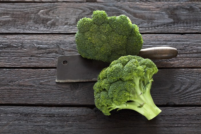 Two broccoli florets and kitchen cleaver on dark wood
