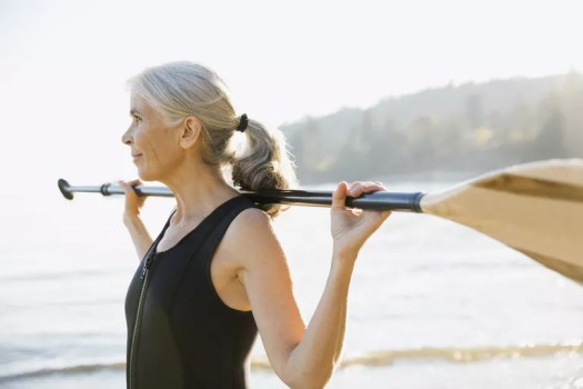Senior woman holding paddle on sunny beach