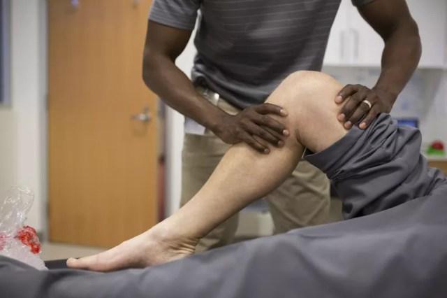 Un physiothérapeute travaille sur la jambe d'un patient.