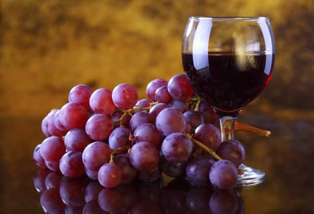 A bunch of grapes and a glass of red wine
