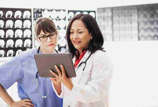 Nurse and doctor looking over tablet