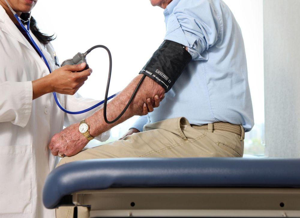 medium resolution of doctor checks man s blood pressure