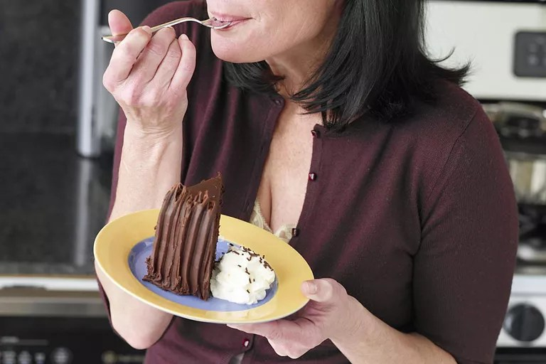 Woman eating cake, eyes closed, close-up