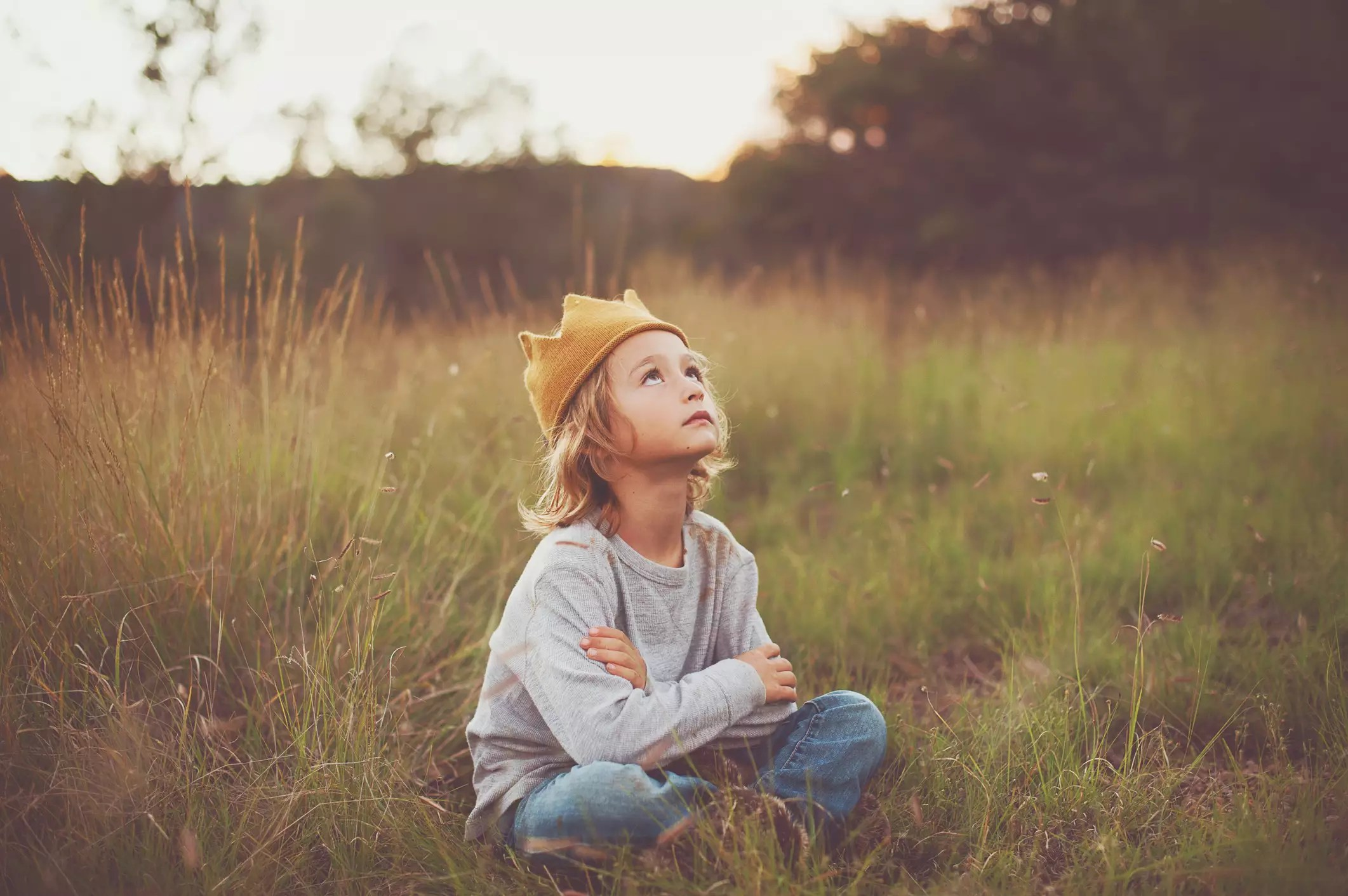 Cute little boy sitting outdoors, wearing crown, looking up at the sky.