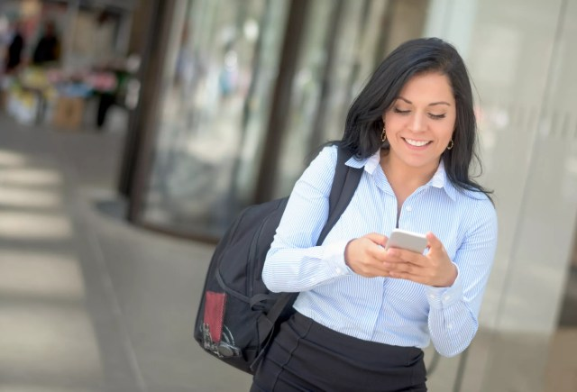 Young woman walking and texting on her phone.