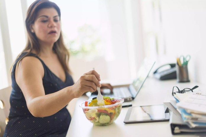 Woman eating salad and using laptop in office