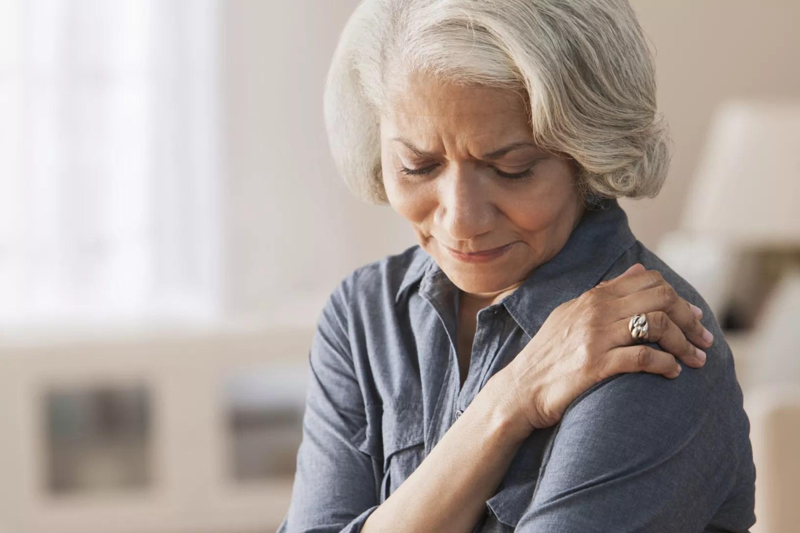 Woman rubbing shoulder in pain