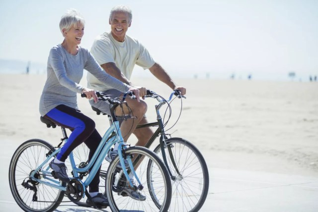 Photo of active older couple riding bicycles.