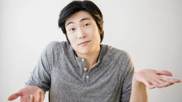 young asian man shrugging