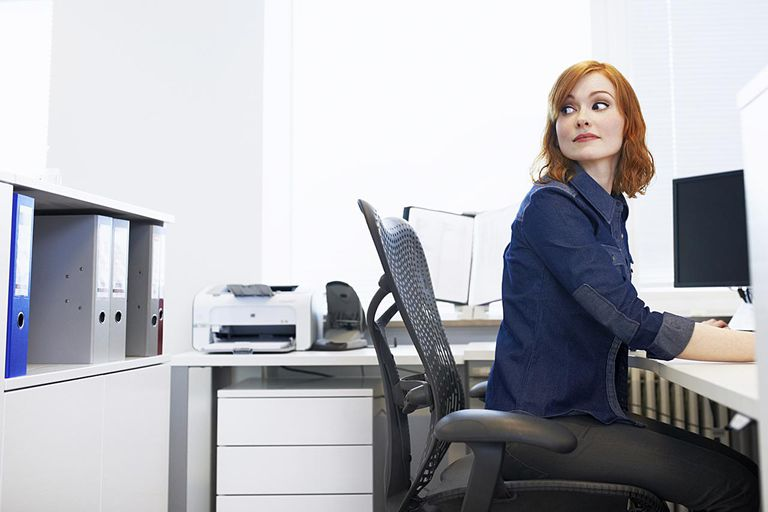 office chair back pain black parsons slipcovers height and hip joint angle young businesswoman sitting at a desk looking over her shoulder
