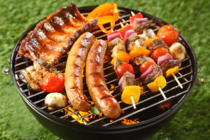Assorted grilled meat on a summer barbecue with sausages, spicy ribs and beef kebabs with vegetables, outdoors on a green lawn