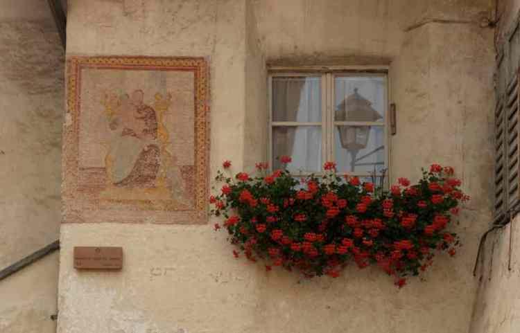 un antico affresco sul balcone di una casa di tesero in trentino alto adige