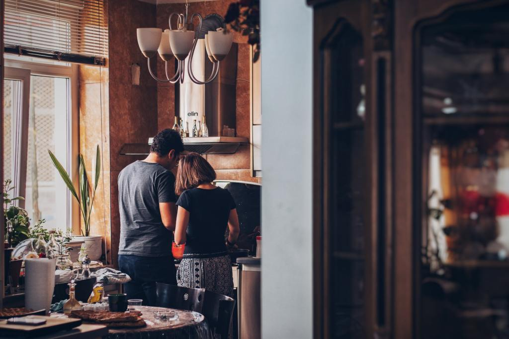 due persone che preparano la cena a casa per risparmiare soldi