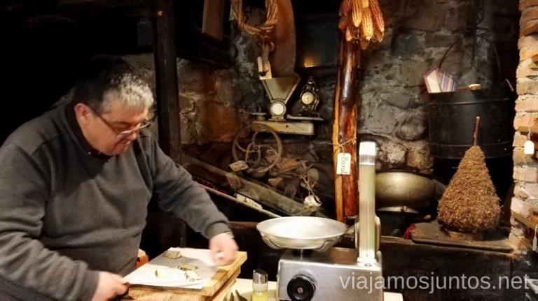 Señor del bar/tienda pesando el queso Senda del Oso en bici, Astrurias