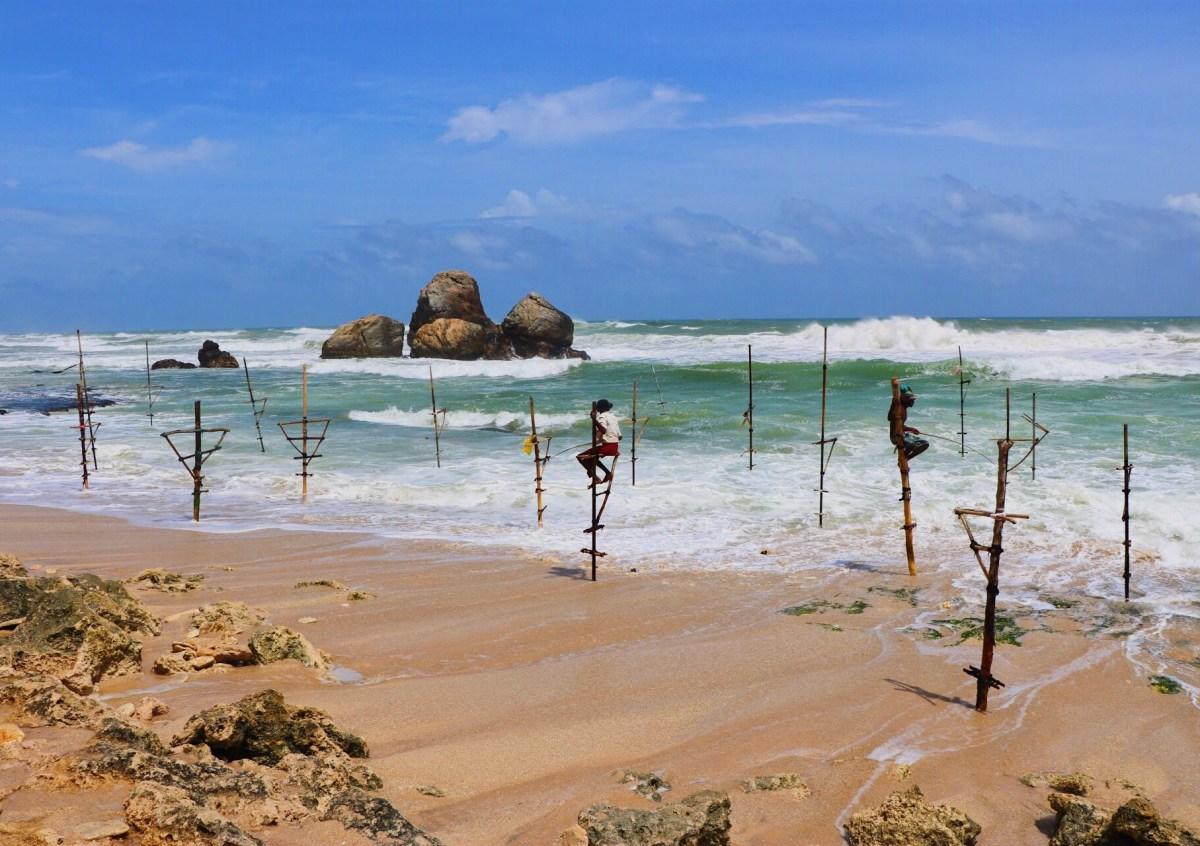 Pescadores aguantando el equilibrio para pescar en la playa de Koggala