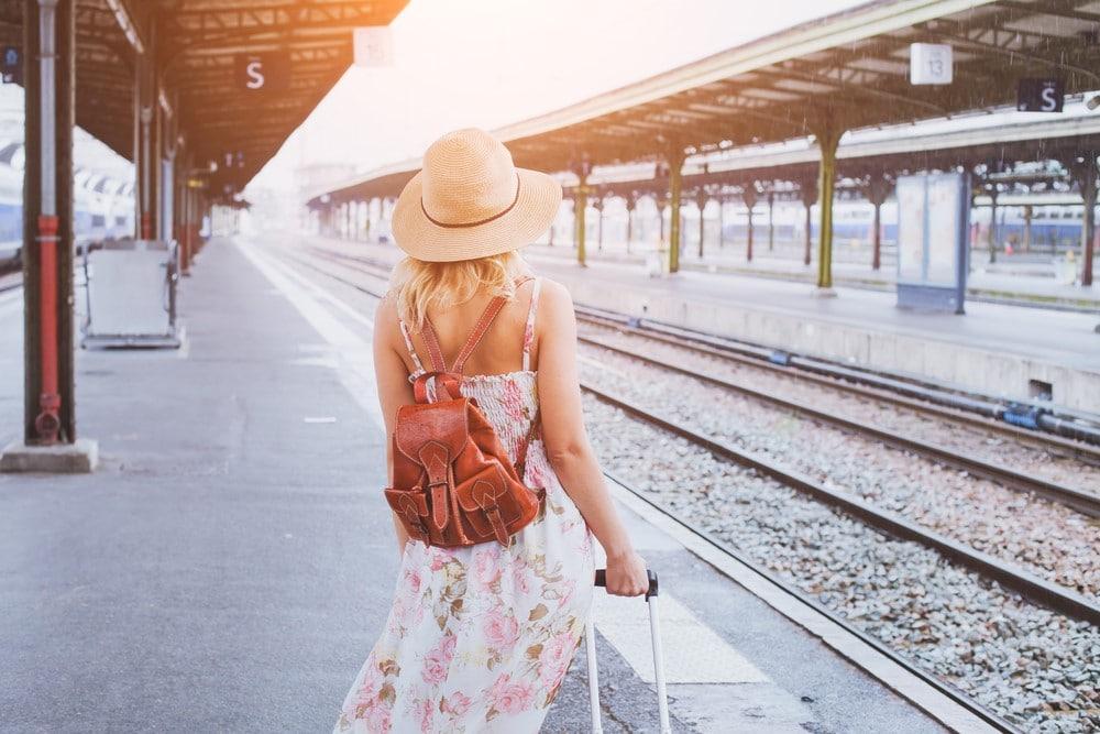 mujer rubia en estación de tren jalando su maleta