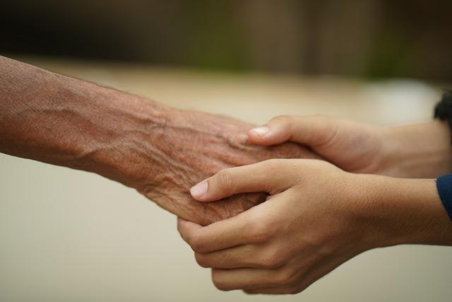 manos de un joven aprentando la mano de un anciano