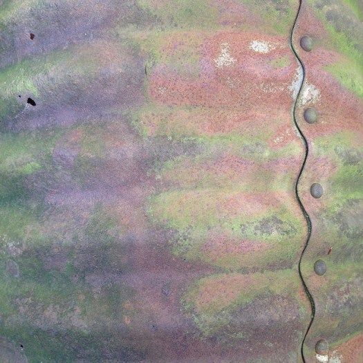 An old corrugated steel pipe, rusted into an extravagant range of colors.