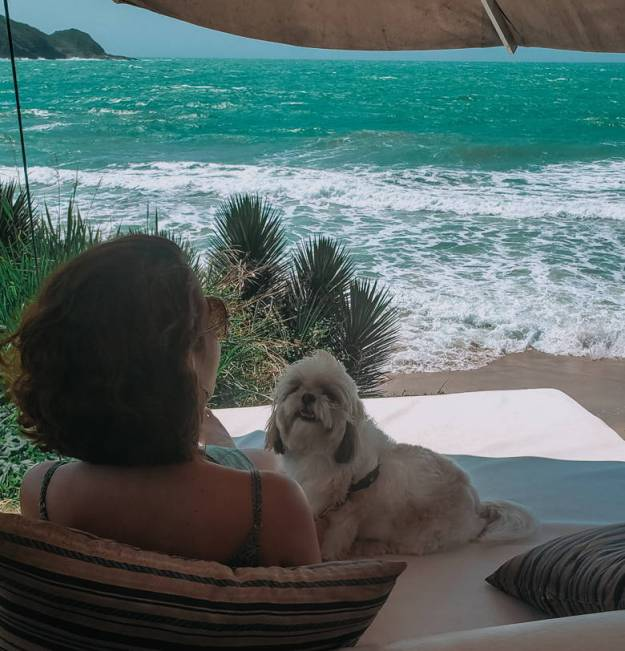 mulher com cachorro frente pro mar