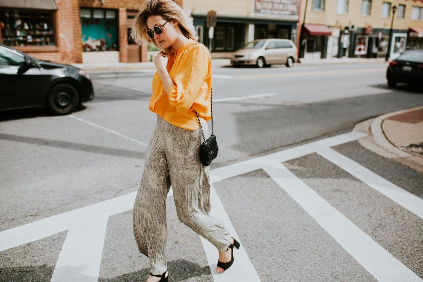 How to Look Like you're From the 70s featured by top US fashion blog, Viciloves: image of a woman wearing a yellow flowy top, silver high waisted pants and TOPSHOP suede platform shoes