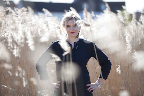 Entrepreneur Wellbeing Coach Victoria Ward stands amid tall grasses, hands on her hips