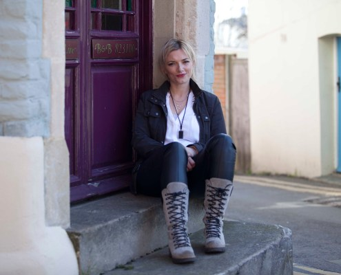 Victoria Ward sits on the steps of a purple door