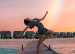 A woman dances joyfully infront of a rainbow