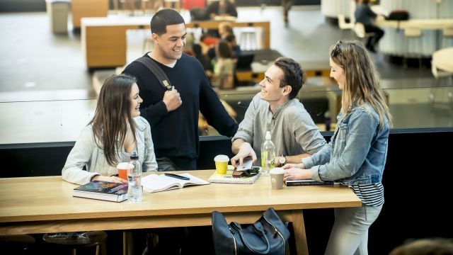 Four students chat in The Hub