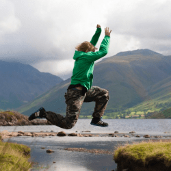Person jumping across a river with mountains in the background