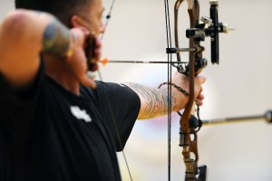Rear shot of a military personnel with compound bow at full draw.