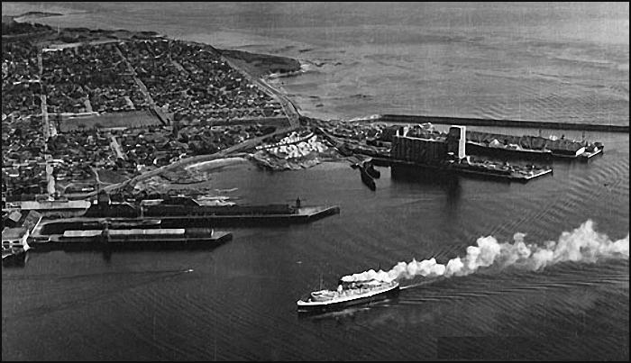 From back to front: the breakwater, Ogden Point Dock A before the construction of the Westcan warehouse, Dock B with the Pacific Grain Terminal, Rithet's Piers (to the left) and a BCSS Princess liner steaming into the harbour.