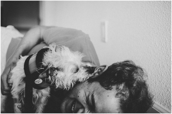 A dog licking a man's face with man laughing
