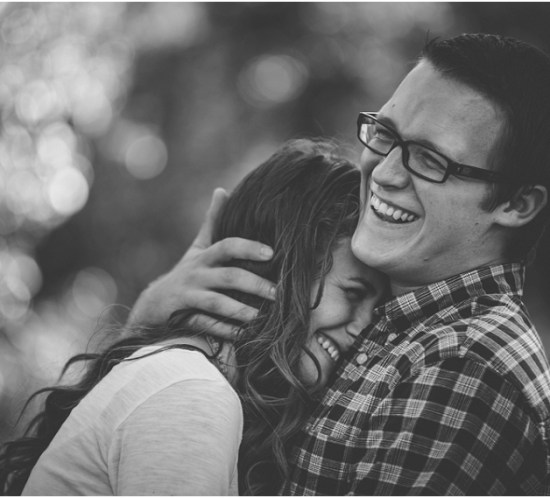 Black and white portrait of a couple laughing and hugging