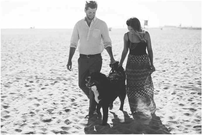 Black and white image of couple walking their dog on a beach