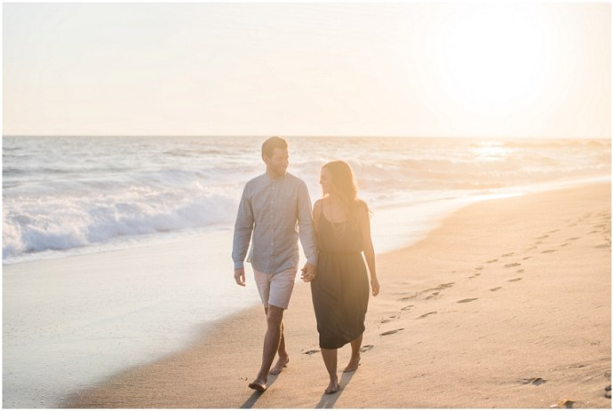 Colour image of a couple walking along an empty beach at sunset