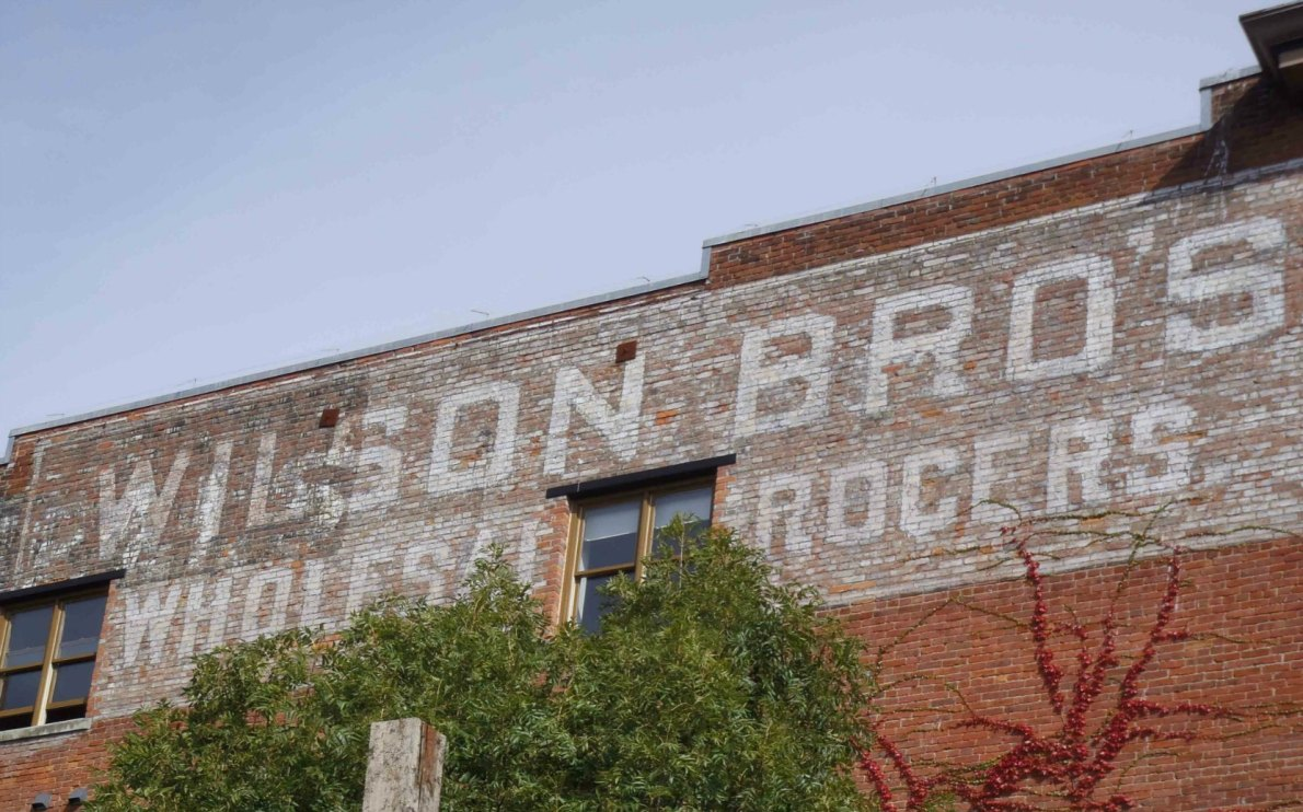 Wilson Brothers Wholesale Grocers sign, possibly dating as early as 1909, is still visible on the west side of 532 Herald Street.