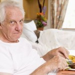 White-haired patient glares as he eats his hospital meal in bed