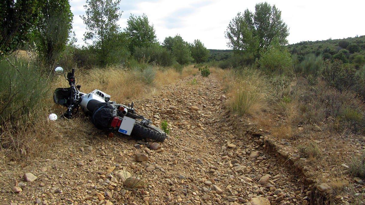 Kawasaki KLR tumbada sobre piedras