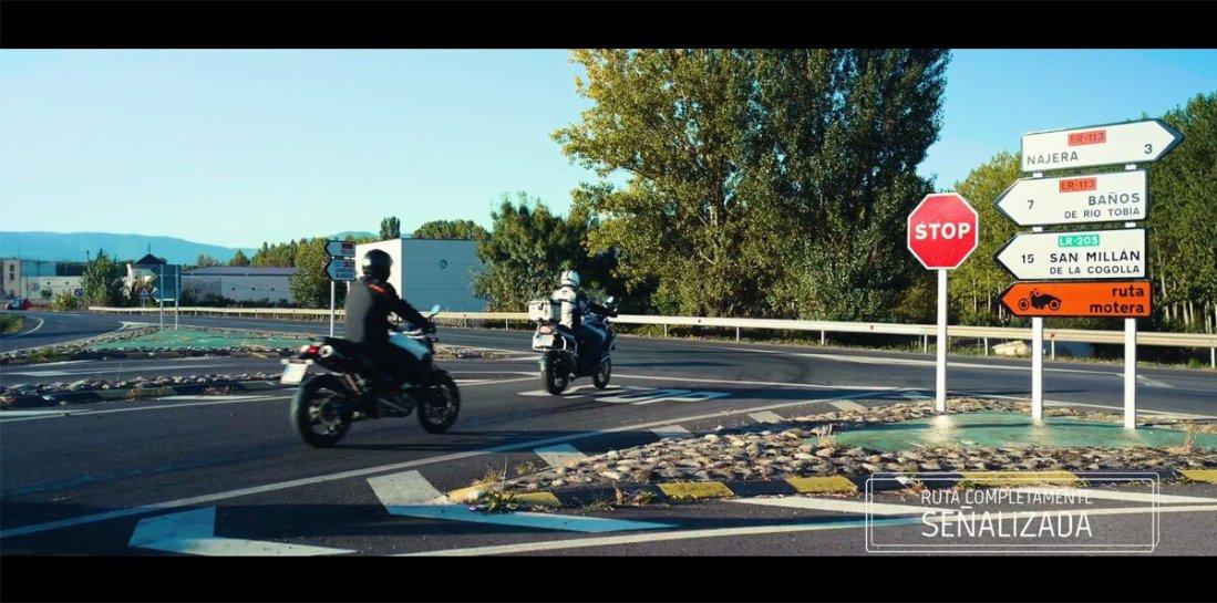 """Dos motos junto a una señal de """"ruta motera"""""""